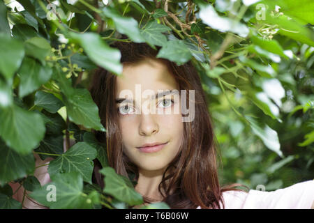 portrait of a beautiful teenage girl behind  foliage - Stock Photo