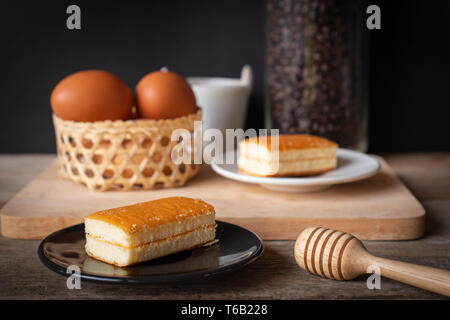 layer vanilla flavoured cake place on black plate on the wooden table there are white plate and coffee bean in glass bottles and bucket of water ceram - Stock Photo