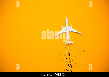 Miniature toy airplane with sparkles on yellow background. Journey - Stock Photo