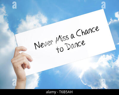 Never Miss a Chance to Dance Sign on white paper. Man Hand Holding Paper with text. Isolated on sky background - Stock Photo