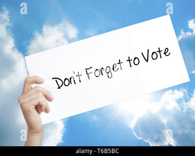 Don't Forget to Vote Sign on white paper. Man Hand Holding Paper with text. Isolated on sky background - Stock Photo