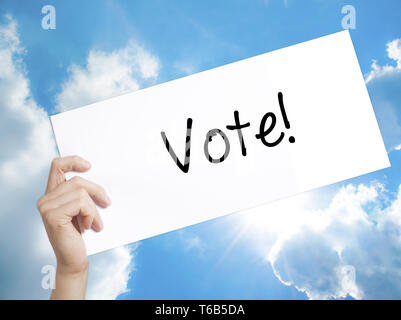 Vote! Sign on white paper. Man Hand Holding Paper with text. Isolated on sky background - Stock Photo