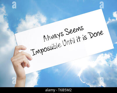 Always Seems Impossible Until it is Done Sign on white paper. Man Hand Holding Paper with text. Isolated on sky background - Stock Photo