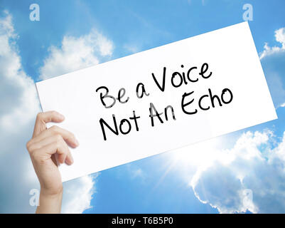 Be a Voice Not An Echo Sign on white paper. Man Hand Holding Paper with text. Isolated on sky background - Stock Photo