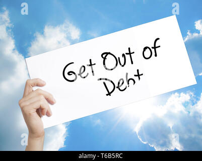 Get Out of Debt Sign on white paper. Man Hand Holding Paper with text. Isolated on sky background - Stock Photo