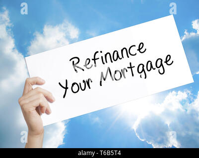 Refinance Your Mortgage Sign on white paper. Man Hand Holding Paper with text. Isolated on sky background - Stock Photo