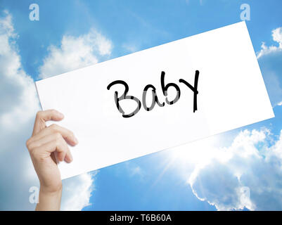 Baby Sign on white paper. Man Hand Holding Paper with text. Isolated on sky background - Stock Photo
