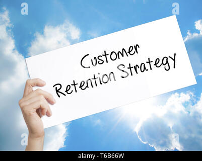 Customer Retention Strategy Sign on white paper. Man Hand Holding Paper with text. Isolated on sky background - Stock Photo