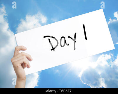 Day 1 Sign on white paper. Man Hand Holding Paper with text. Isolated on sky background - Stock Photo