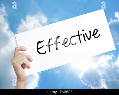 Effective Sign on white paper. Man Hand Holding Paper with text. Isolated on sky background. - Stock Photo