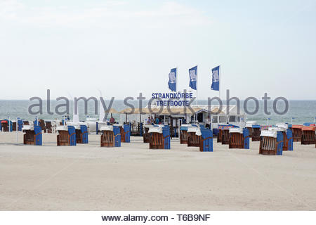 Roofed wicker beach chairs for rent in Warnemunde Germany - Stock Photo