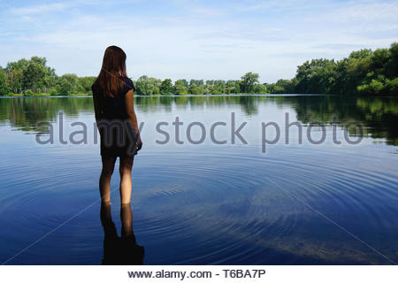young woman standing in lake - Stock Photo