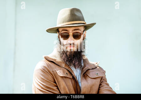 Portrait of a stylish bearded man dressed in jacket and hat on the light turquoise background outdoors - Stock Photo