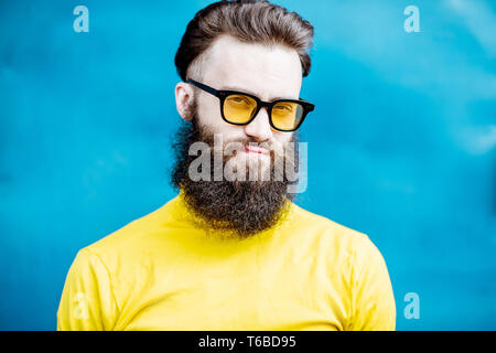Close-up portrait of a confused bearded man in yellow sweater and sunglasses on the blue background - Stock Photo