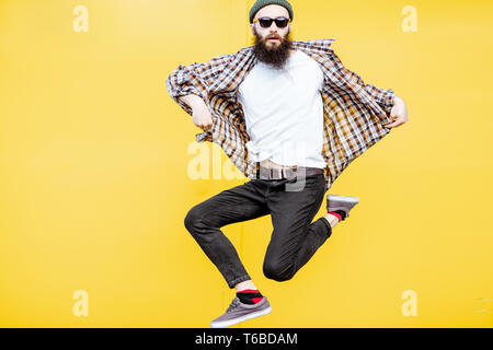 Portrait of a cool stylish man in checkered shirt jumping on the bright yellow background - Stock Photo