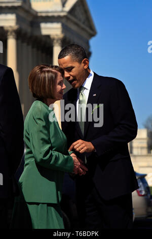 Speaker Nancy Pelosi and the 44th President of the United States, Barack Obama, join at the stairs of the US Capitol on St. Patricks Day after securing the Obamacare bill. - Stock Photo