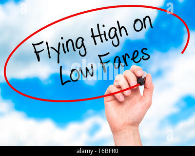 Man Hand writing Flying High on Low Fares with black marker on visual screen - Stock Photo