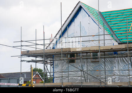Scaffolding on side of new  house - Stock Photo