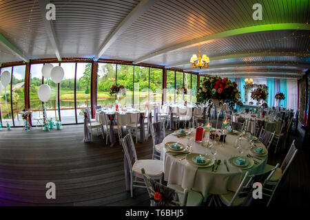 Luxury decorated place for wedding reception catering in restaurant next to the pond. Guest tables in luxury decorated wedding banquet room. Festive d - Stock Photo
