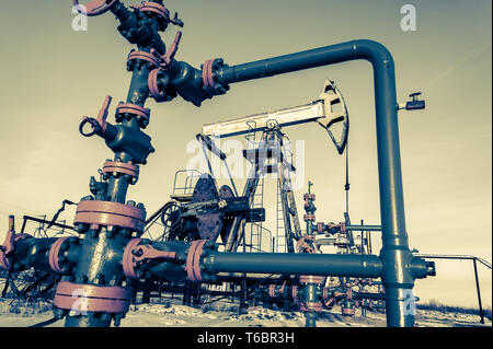 Group of wellhead. Oilfield with sand ground. - Stock Photo