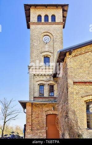 HDR shot of a yellow brick building with clock tower - Stock Photo