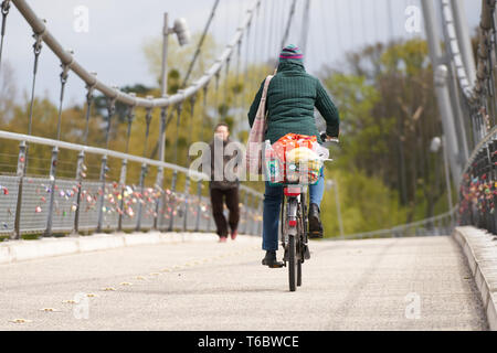 cyclist and pedestrian on a suspension bridge in Magdeburg - Stock Photo