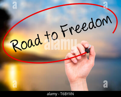 Man Hand writing Road to Freedom with black marker on visual screen. - Stock Photo