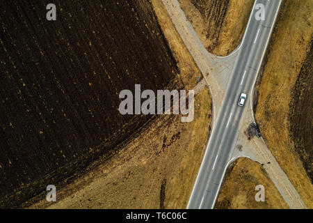 Aerial view of single white car driving on road through plain countryside in cold winter afternoon without snow - Stock Photo