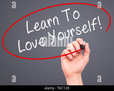 Man Hand writing Learn To Love Yourself with marker on transparent wipe board - Stock Photo