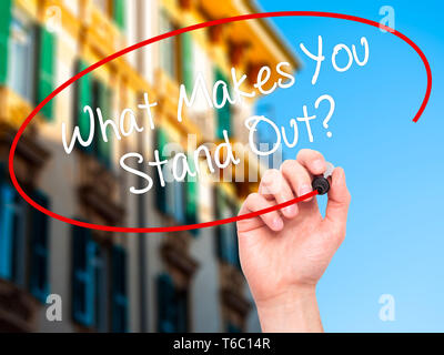 Man Hand writing What Makes You Stand Out? with black marker on visual screen - Stock Photo