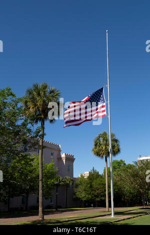 The Stars and Stripes flies at half-staff in Charleston, South Carolina, USA. The flag pole is outside of the old Citadel at Marion Square. - Stock Photo