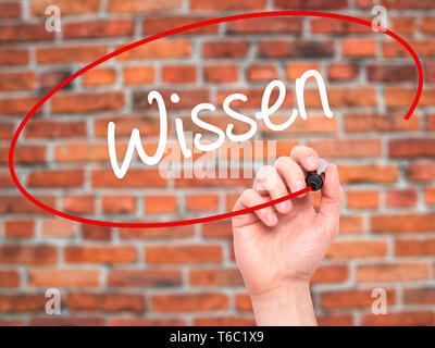 Man Hand writing Wissen (Know in German)  with black marker on visual screen - Stock Photo