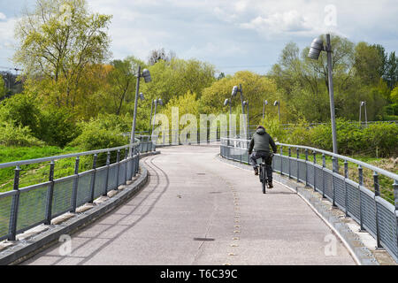 Cyclist on the bridge to Herrenkrug Park in Magdeburg - Stock Photo