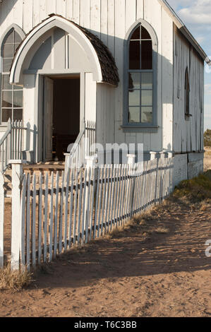 Old white church front with wooden picket fence in front - Stock Photo