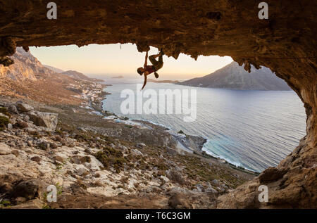 Young woman climbing in cave at sunset, Kalymnos Island, Greece - Stock Photo