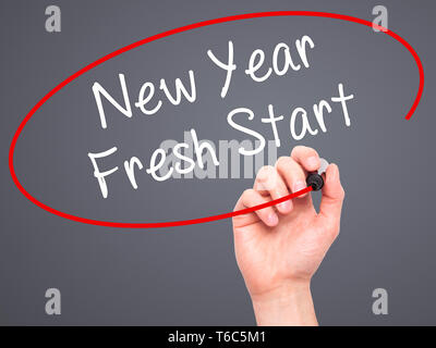 Man Hand writing New Year Fresh Start with black marker on visual screen - Stock Photo