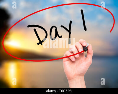 Man Hand writing Day 1 with black marker on visual screen - Stock Photo