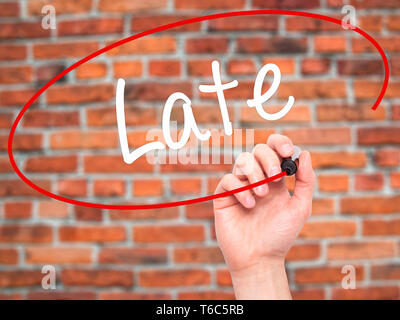Man Hand writing Late with black marker on visual screen - Stock Photo