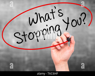 Man Hand writing What's Stopping You?  with black marker on visual screen - Stock Photo