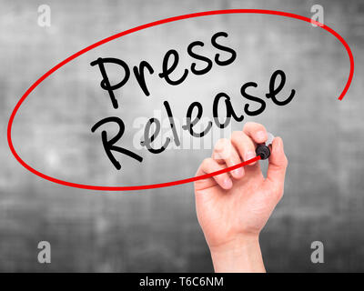 Man Hand writing Press Release with marker on transparent wipe board - Stock Photo