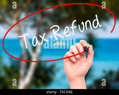 Man Hand writing Tax Refund with black marker on visual screen - Stock Photo
