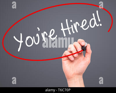Man Hand writing You're Hired! with black marker on visual screen - Stock Photo