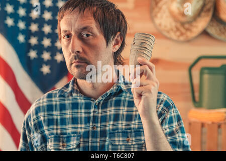 American farmer with biodegradable peat pots, adult caucasian male holding soil containers ready for planting - Stock Photo
