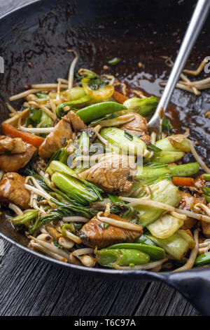 Traditional stir fried Chicken Gung Bao with Vegetable as close-up in Wok - Stock Photo