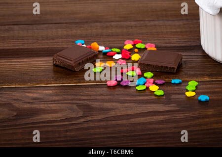 colorful sprinkles and chocolate pieces on wooden background with copy space. - Stock Photo