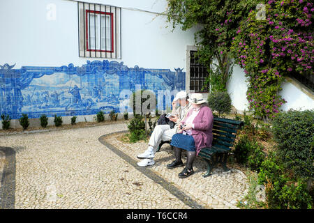 Tourists looking at a historical depiction of Seige of Lisbon 1147 commemorated in blue wall tiles azulejos in Alfama Lisboa Portugal  KATHY DEWITT - Stock Photo