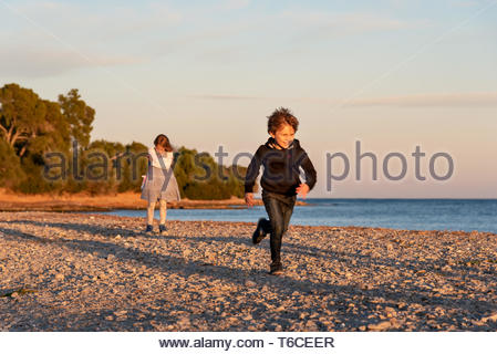 Siblings playing in a sunny Autumm sunset at the beach. Happy young boy runs away from her sister, while she gets upset. - Stock Photo