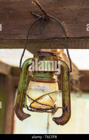 Pendant paraffin lamp, rusting and abandoned, hanging in a shed, Kilwinning, Scotland - Stock Photo