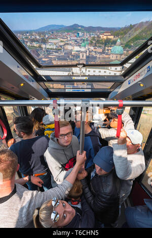 Funicular ride, view of the interior of a crowded funicular carriage transporting tourists to Salzburg Castle (Hohensalzburg), Austria. - Stock Photo