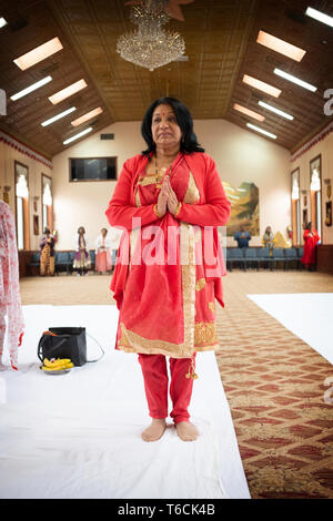 An attractive middle aged  Hindu woman in a beautiful sari with her hands clasped in a temple in Jamaica, Queens, New York City. - Stock Photo